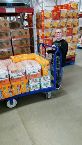 kid happily pushing the cart of groceries
